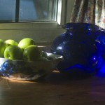 still life of green apples and blue pitcher