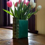 tulips in book vase on vintage table